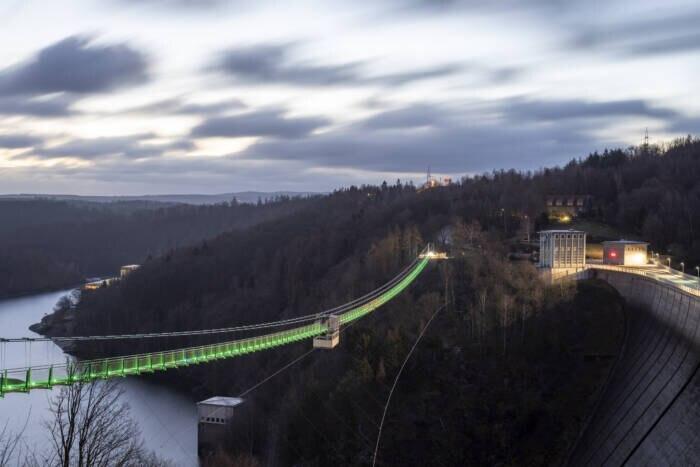 Eine beleuchtete Brücke hängt über einer Schlucht