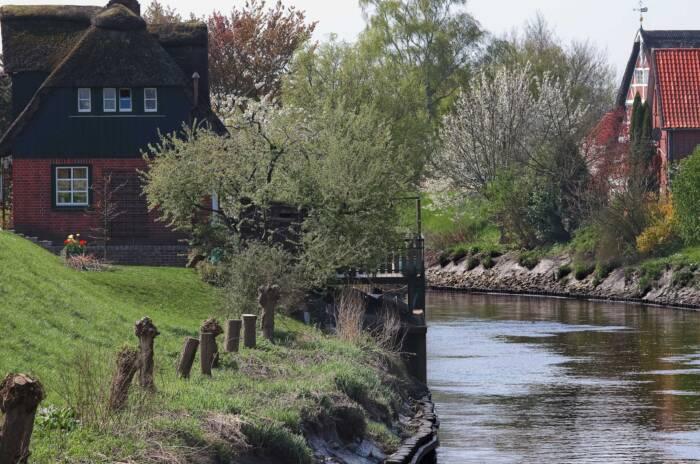 Ein Fluss, der an zwei Häusern vorbeifließt