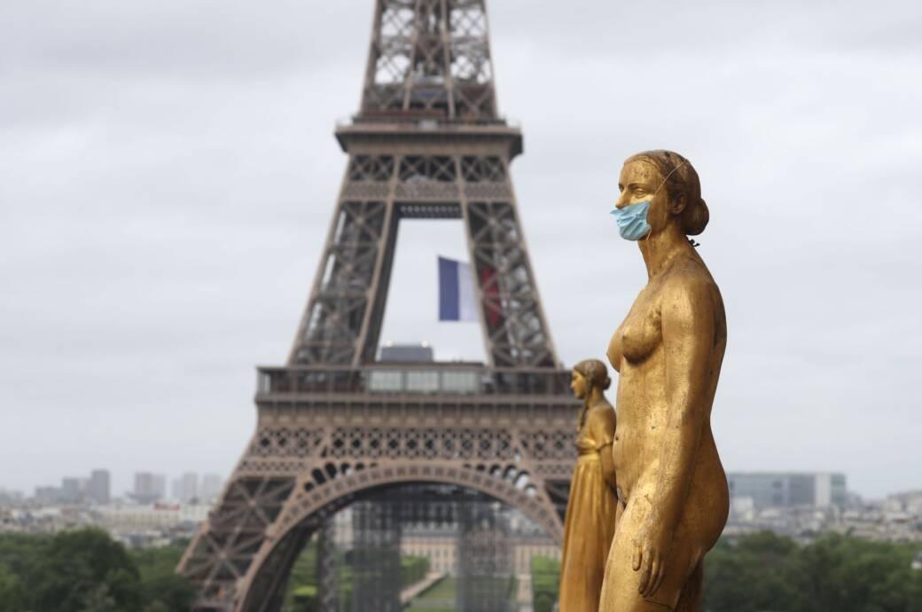 Statue mit Maske vorm Eiffelturm in Paris, Frankreich