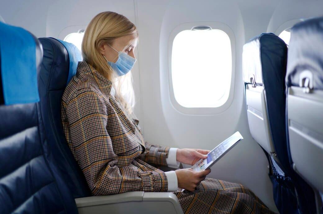 Frau im Flugzeug mit Maske